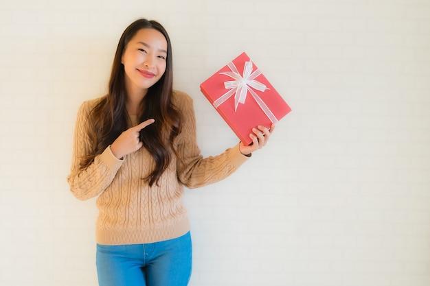 Sorriso felice della bella giovane donna asiatica del ritratto con il contenitore di regalo