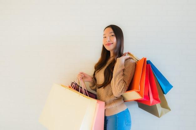 Sorriso felice della bella giovane donna asiatica del ritratto con il sacchetto della spesa