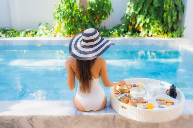 Sorriso felice della bella giovane donna asiatica del ritratto con la prima colazione di galleggiamento in vassoio sulla piscina