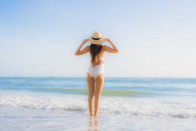 Sorriso felice della bella giovane donna asiatica del ritratto intorno alla spiaggia dell'oceano del mare