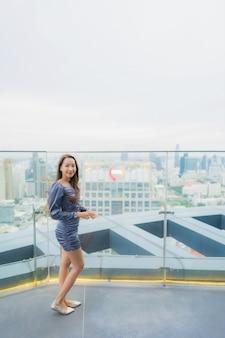 Sorriso felice della bella giovane donna asiatica del ritratto sul ristorante della cima del tetto intorno alla vista della città