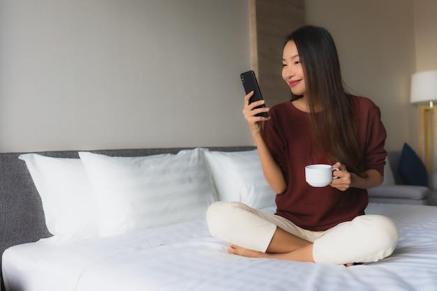 Sorriso felice delle belle giovani donne asiatiche del ritratto con caffè e il telefono cellulare
