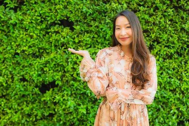 Sorriso felice delle belle giovani donne asiatiche del ritratto intorno all'aperto