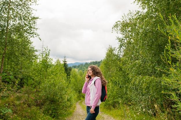Sorriso femminile della ragazza e telefono cellulare della tenuta sulla cima delle montagne.