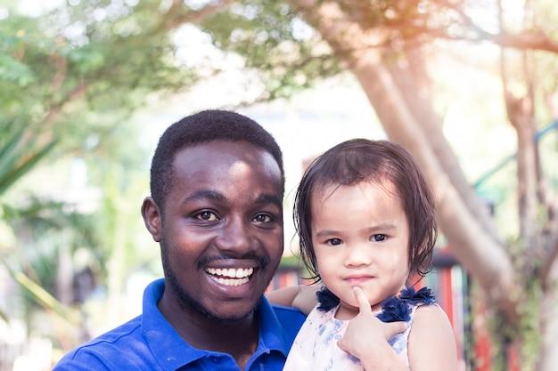 Sorriso l'uomo africano sta portando una ragazza asiatica bambino con amore e felice.