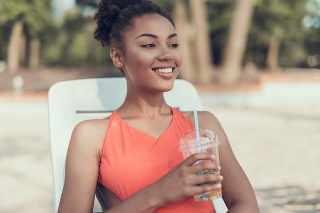 Sorriso la donna sta bevendo e riposando sul fiume