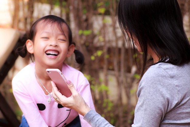 Sorriso ragazza bambino felice con la riproduzione di smartphone.
