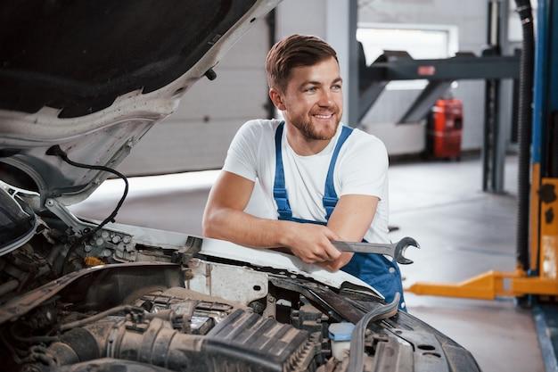 Sorriso sincero. l'impiegato con l'uniforme di colore blu lavora nel salone dell'automobile