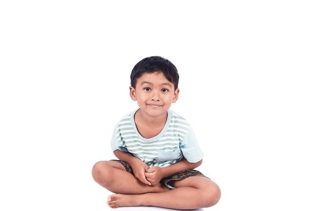Sorriso sveglio del ragazzino e seduta sul pavimento