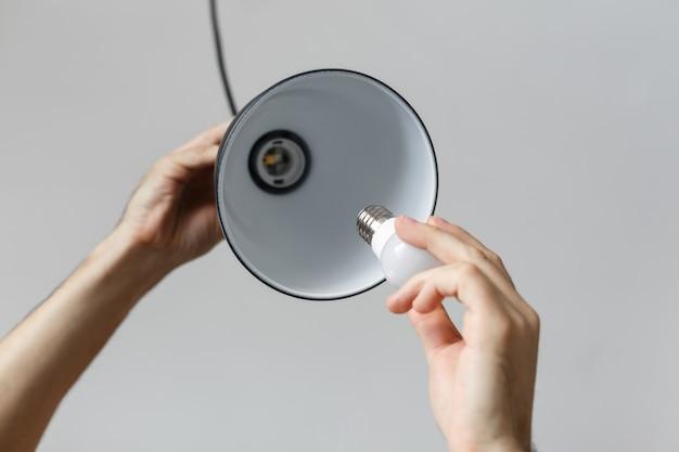 Sostituzione della lampadina per lampadina a led nella lampada da terra in colore nero. su sfondo grigio chiaro
