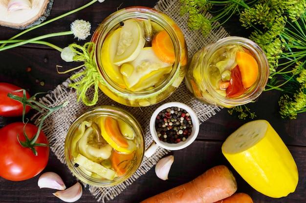 Sottaceti: assortimento di verdure in barattoli di vetro su un legno scuro. la vista dall'alto