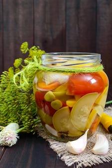 Sottaceti: assortimento di verdure (zucchine, pepe, carote, pomodoro, piselli) in barattoli di vetro su un legno scuro.