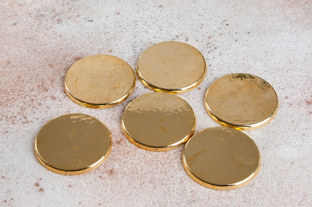 Sottobicchieri d'oro vintage su sfondo concreto.