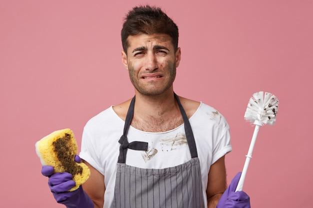 Sottolineato triste studente bello in piedi al muro rosa con scopino e spugna piagnucolare perché odia i lavori domestici ma deve fare le pulizie
