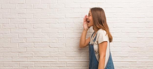 Sottotono di gossip di sussurro della donna giovane dei pantaloni a vita bassa