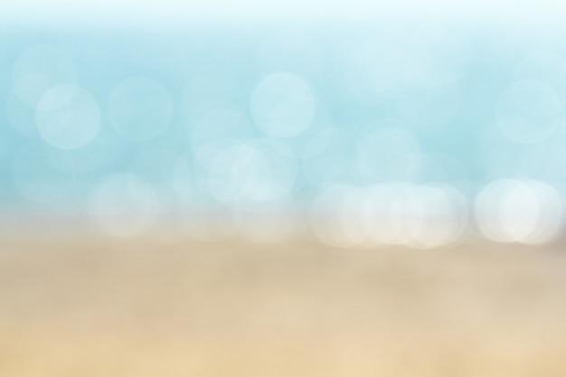 Sottragga la spiaggia tropicale della sfuocatura con il bokeh di bellezza nell'ambito della luce solare sull'onda