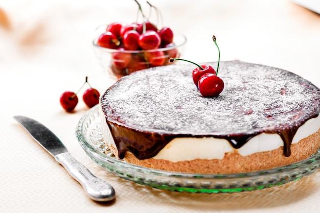 Soufflé di bird's milk, ricoperto di glassa al cioccolato e decorato con succose ciliegie mature