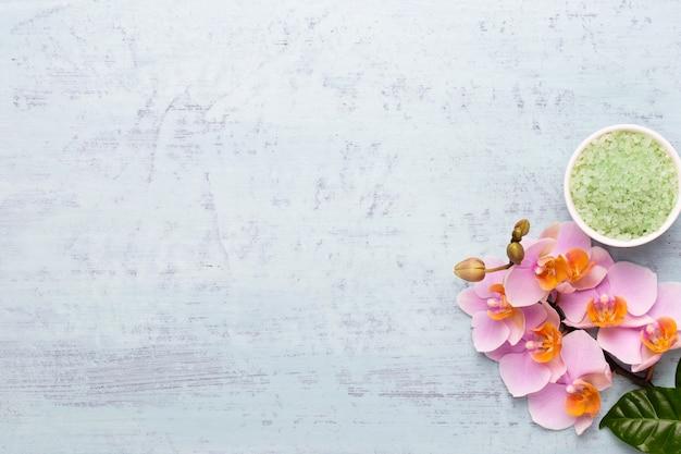 Spa aromaterapia sfondo, laici piatta di vari prodotti per la cura di bellezza decorata con semplici fiori di orchidea.