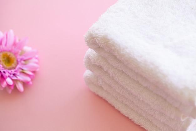 Spa. asciugamani di cotone bianco utilizzare nel bagno spa su rosa. asciugamano . foto per hotel e sale massaggi. purezza e morbidezza. asciugamano tessile