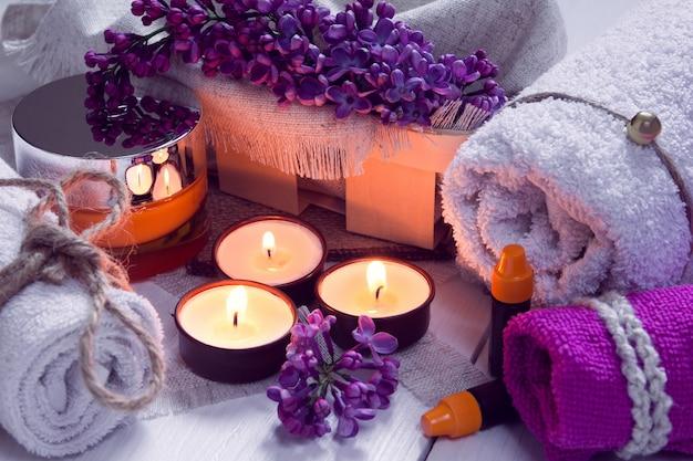 Spa composta da asciugamani, lilla, candele, panna e olio