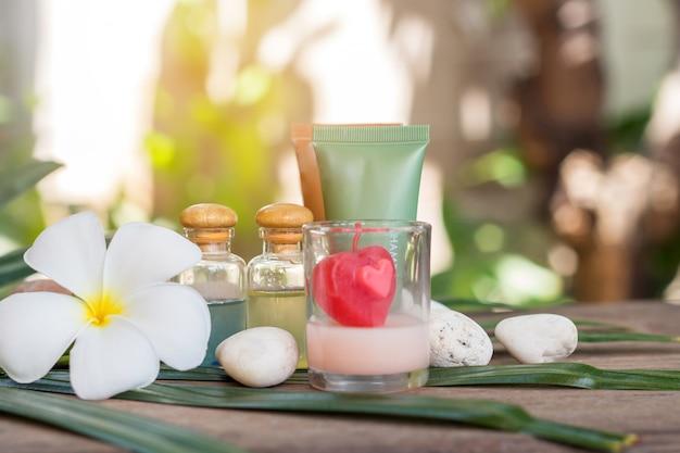 Spa di prodotti di aromaterapia di massaggio terapeutico con fiori di plumeria o frangipani.