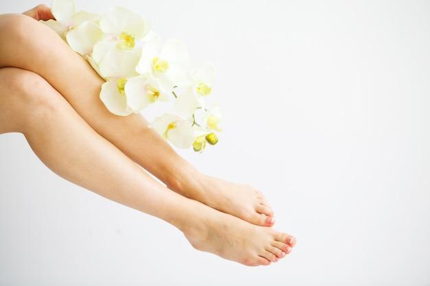 Spa. donna che massaggia le gambe che si siedono sul bianco