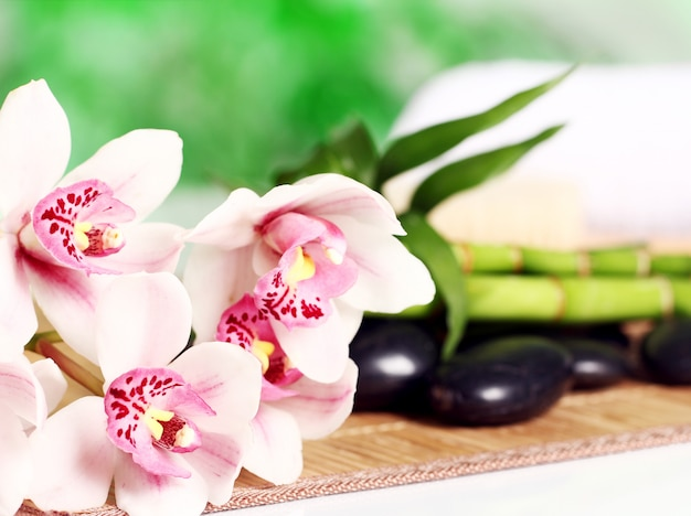 Spa e benessere, massaggio pietre e fiori sulla tovaglia in legno