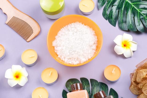 Spa e prodotti per la cura del corpo distesi. scrub corpo, sale da bagno, lozione idratante, candele e foglie su woodentable