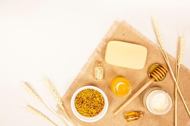 Spa oggetto e polline d'api con grano raccolto su tessuto di iuta