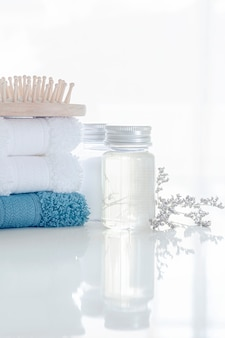 Spa set con pila di asciugamani puliti, bottiglia di olio, pettine in legno e fiori