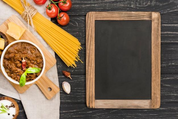 Spaghetii ingredienti e lavagna alla bolognese