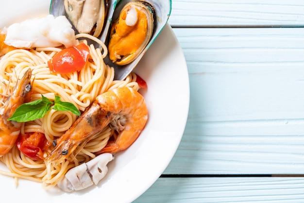 Spaghetti ai frutti di mare con vongole, gamberi, calamari, cozze e pomodori