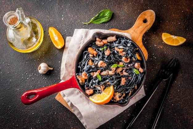 Spaghetti al nero di seppia con frutti di mare, olio d'oliva e basilico