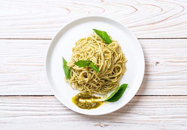 Spaghetti al pesto, olio d'oliva e foglie di basilico.