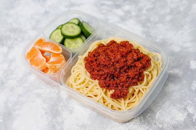 Spaghetti alla bolognese da asporto in una scatola da pranzo in plastica con bevanda disintossicante e fetta di frutta sulla luce