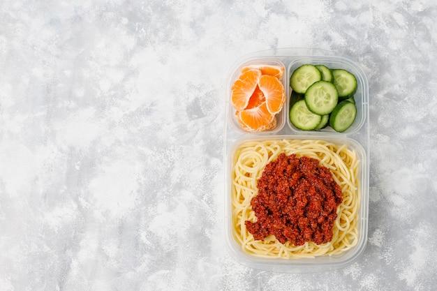 Spaghetti alla bolognese da asporto in una scatola di pranzo in plastica e fetta di frutta sulla luce
