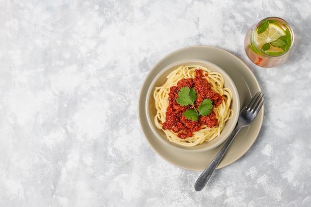 Spaghetti alla bolognese e limonata su cemento grigio