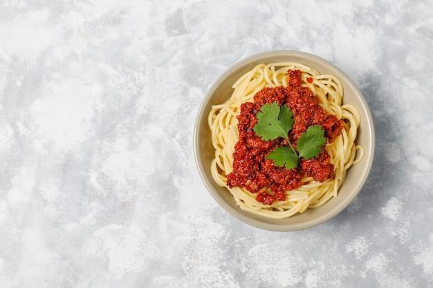 Spaghetti alla bolognese su cemento grigio