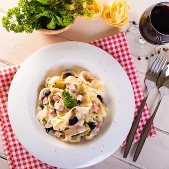 Spaghetti alla carbonara con prosciutto, olive nere, formaggio, verdure e un bicchiere di vino rosso bianco.