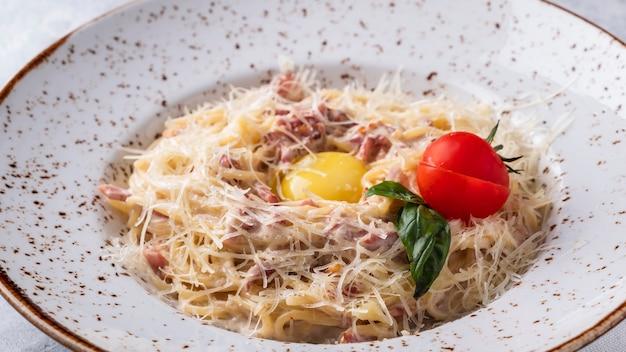 Spaghetti alla carbonara, uova, parmigiano e salsa di panna. avvicinamento