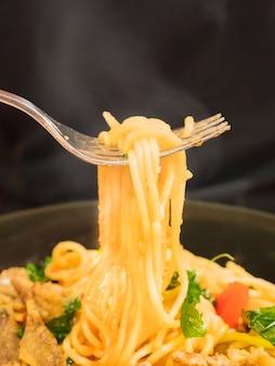 Spaghetti caldi e piccanti con forchetta su sfondo nero