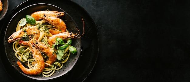 Spaghetti con pesto e gamberi serviti sul piatto
