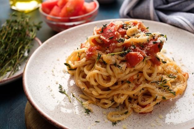 Spaghetti con pomodori e timo in un piatto su un tavolo blu