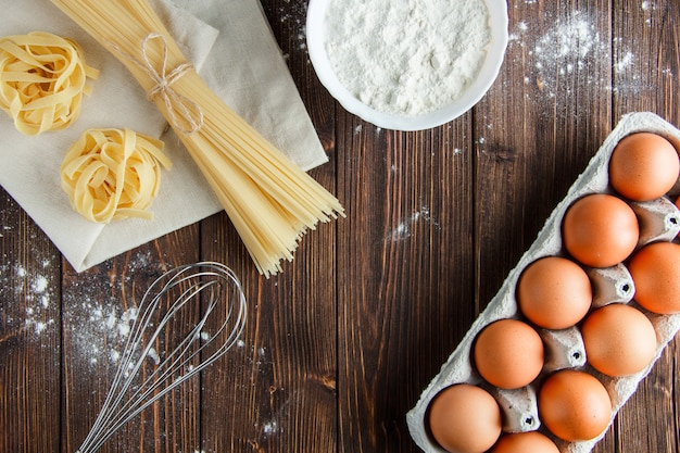 Spaghetti con uova, farina, frusta, fettuccine su asciugamano di legno e cucina, piatto disteso.