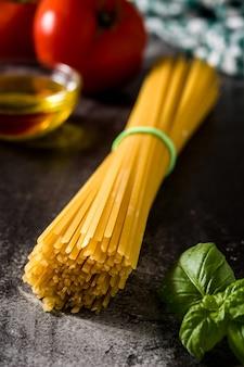 Spaghetti crudi dell'alimento italiano con gli ingredienti su fondo nero