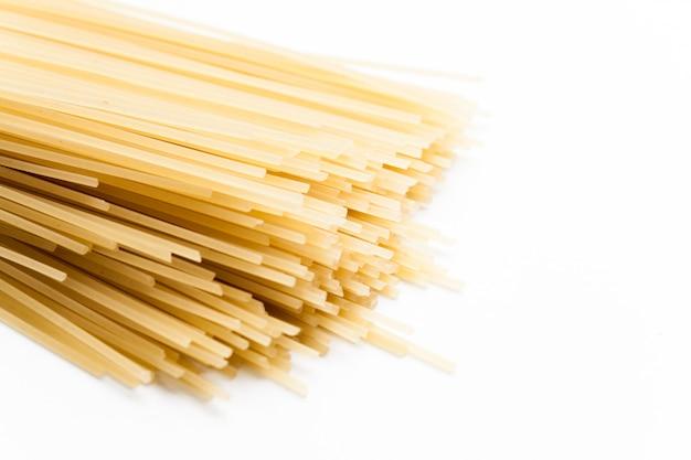 Spaghetti crudi su fondo bianco.