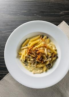 Spaghetti deliziosi con funghi fritti in salsa di panna acida