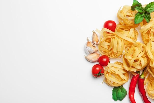 Spaghetti della pasta con gli ingredienti per la cottura della pasta su un fondo bianco, vista superiore.