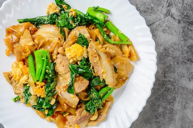 Spaghetti di farina di riso fresco saltati in padella con carne di maiale affettata, uovo e cavolo. tagliatella veloce saltata in padella.