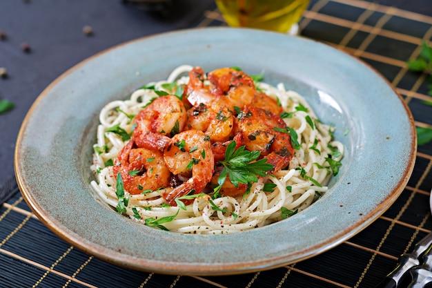 Spaghetti di pasta con gamberetti, pomodoro e prezzemolo tritato. cibo salutare. pasto italiano